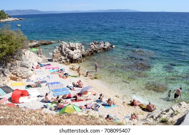Tourists are sunbathing on the rocky shoreline and enjoying the sunshine and swiming in the Mediterranean Sea at August 20, 2017 in Rabac beach, Croatia.