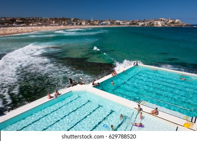 Tourists swimming at Bondi Icebergs swimming pool, with the famous Bondi Beach in the background, Sydney, Australia, January 2013. Note the narrow depth of field of the tilt-shift lens