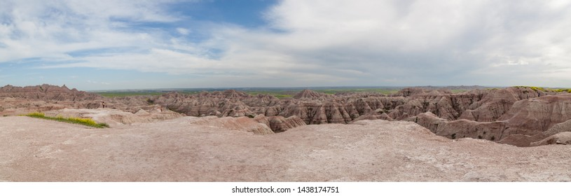 Tourists take in a panoramic view of dramatic mountain formations carved out by erosion showing layers of rocks with spring wildflowers below in Badlands National Park, South Dakota.