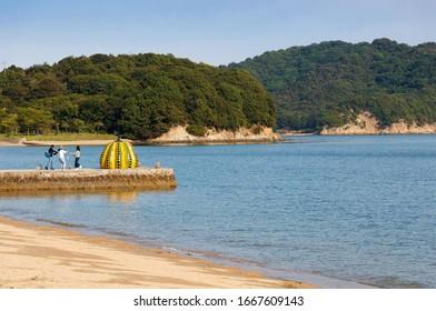 Tourists taking photos before the Yellow Pumpkin, a famous artwork of Yayoi Kusama, in the beautiful scenery of a sandy beach by Seto Inland Sea under blue sunny sky, in Naoshima Island, Kagawa, Japan