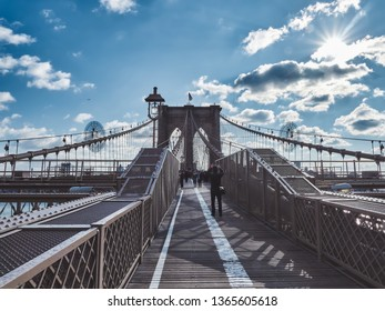 Tourists taking pictures on the Brooklyn Bridge and walking around it.