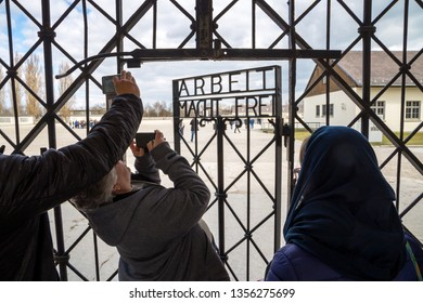 """Tourists are taking pictures of the """"Work sets you free"""" (Arbeit macht frei) sign on the gate of Dachau concentration camp memorial site. Dachau, Germany - Mar 26. 2019."""