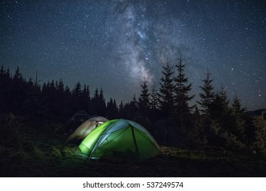 Tourists tents in the wood under the Milky Way