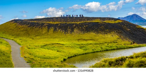 Tourists at the top of pseudo craters aka volcanic near Skutustadir and lake Myvatn on Iceland