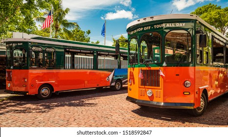 Tourists  travel on historic, orange Trolley Buses of Key West, Florida