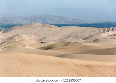Tourists travel through the dunes in the Atacama Desert - Oasis of Huacachina, Peru, South America