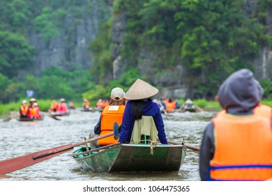 Tourists traveling in boat along the Ngo Dong River and taking picture of the Tam Coc, Rower using feet to propel oars. Tam Coc, Ninh Binh, Vietnam.