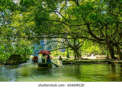 Tourists traveling in boat along the Ngo Dong River taking picture of the Tam Coc, Ninh Binh, Vietnam. Rower using her feet to propel oars. Landscape formed by karst towers and rice fields in Vietnam