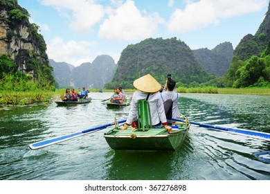 Tourists traveling in boats along the Ngo Dong River at the Tam Coc portion, Ninh Binh Province, Vietnam. Rowers using their feet to propel oars. Landscape formed by karst towers and rice fields.