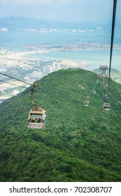 Tourists is traveling by cable car over mountain. The transportation between bottom and peak of mount.