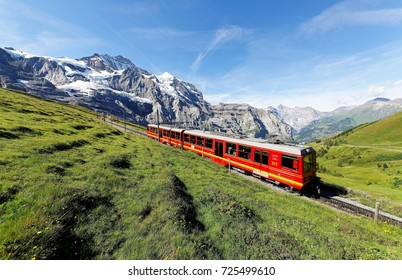 Tourists traveling on a cogwheel train of the famous Jungfrau Railway from Jungfraujoch (Top of Europe) to Kleine Scheidegg on a green grassy hillside under sunny sky, in Bernese Oberland, Switzerland
