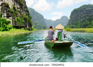 Tourists traveling in small boat along the Ngo Dong River at the Tam Coc portion, Ninh Binh Province, Vietnam. Rower using her feet to propel oars. Landscape formed by karst towers and rice fields.