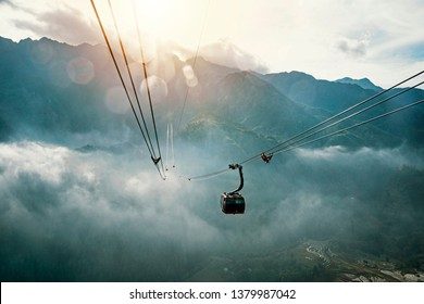 tourists travelling in transportation machine basket on fansipan mountain at sapa north of Vietnam. the sun sets behind mount Fansipan.
