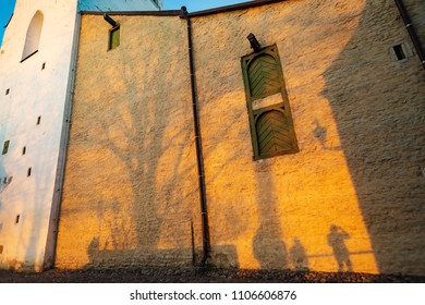 Tourists, tree and photographer casting shadows on sunset colored historical building of The Cathedral of Saint Mary the Virgin in Tallinn Old Town, Estonia