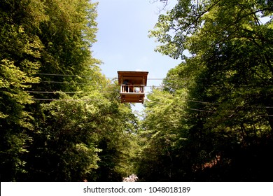 The tourists use the wooden house shape simple hand-powered cable-cars for crossing rivers in Japan.