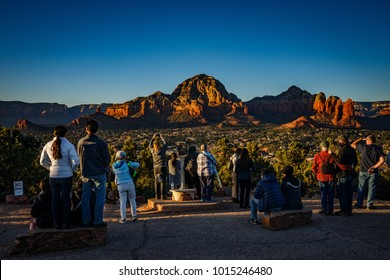 Tourists view Sedona, Arizona, surrounded by red-rock buttes, steep canyon walls and pine forests, is seen at Sunset from Airport Mesa is seen January 24, 2018.