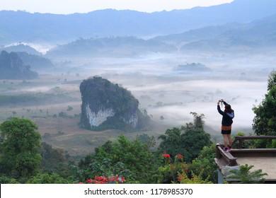 tourists at Viewpoint beautiful sunshine at misty morning mountains ,Phulangka National Park, Payao Province,thailand