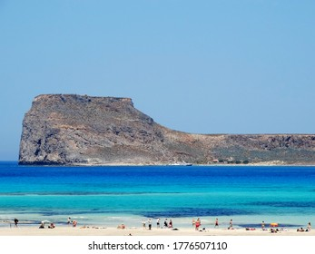 Tourists visit Balos in Crete, Greece and do sunbathing at the beach. The Gramvousa Peninsula forms the westernmost of the two pairs of peninsula in Crete and the western part of Kissamos Bay.