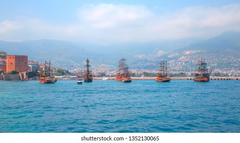 Tourists visit the peninsula of Alanya with pirate ships on the background ancient shipyard and red tower - Alanya, Antalya