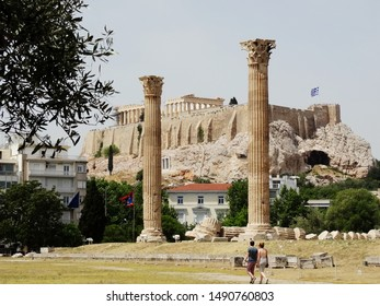 Tourists visit Temple of Olympian Zeus in Athens in Greece with The Parthenon Temple on hill in sight.  Temple of Olympian is also known as the Columns of the Olympian Zeus.