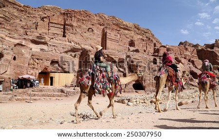 Tourists visiting the ancient ruins of Petra on camels , Jordan