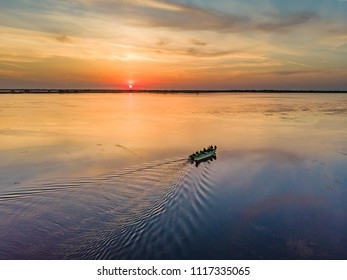 Tourists visiting Danube Delta at sunset in a motor boat. Sunset in Danube Delta (Delta Dunarii), Europe, Romania