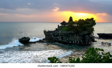tourists wading out to tanah lot temple at sunset