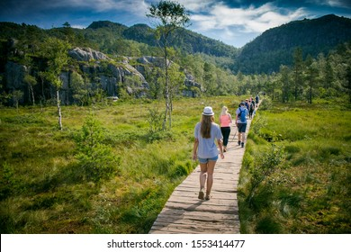 Tourists walk along the path to the mountains. Log wooden bridge on the way to the Pulpit Rock, Norway