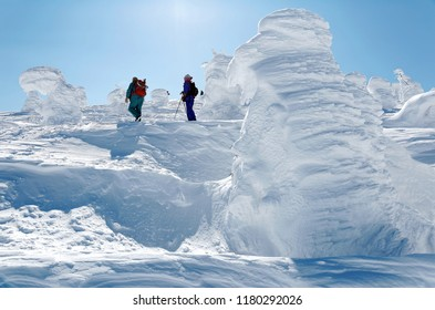 Tourists walk amid giant Juhyo (snow covered ice trees or snow monsters) on the snowy mountainside under blue clear sky in Zao hot spring (onsen) & ski resort on a sunny winter day, in Yamagata, Japan