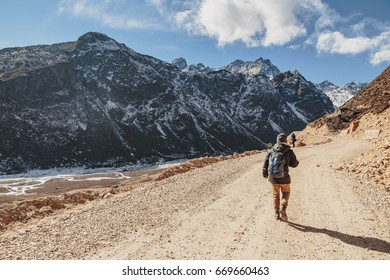 Tourists walk to black mountain with snow on the top and brown mountain with Houses and glacial trace on yellow stone ground at Thangu and Chopta valley in winter in Lachen. North Sikkim, India.