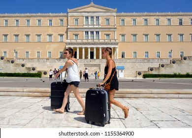 Tourists walk in front of the Greek Parliament building in Athens, Greece on Aug. 13, 2018