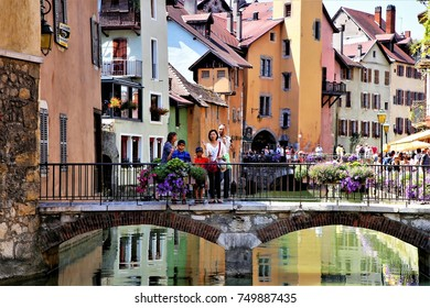 tourists walked across a medieval bridge and visited the famous town of attraction, Annecy, France, July 31, 2015