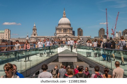 Tourists walking across the Millennium Bridge in the city of London, England with St Pauls Cathedral behind on a glorious sunny summers day on 3rd June 2017