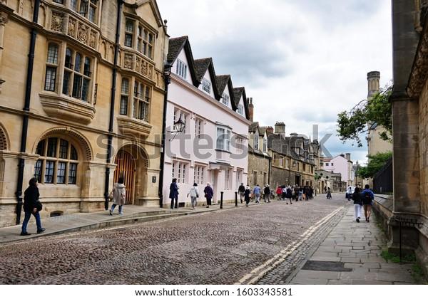 Tourists are walking along the Merton street opposite the Merton college, University of Oxford. Photo was taken on 05/06/2019.