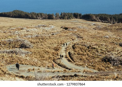 Tourists walking along the Storr trail on the Isle of Sky in Scotland on a warm sunny day