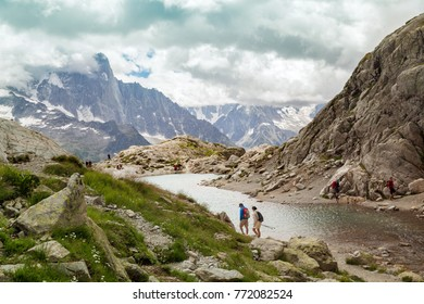 Tourists are walking around mountain lake in overcasted day