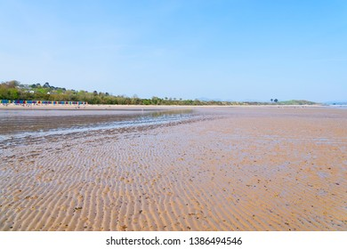 Tourists walking in the distance on the soft, rippled sand of Llanbedrog beach at low tide.