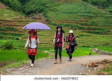 Tourists are walking on a very steep road in the mountains of Sapa with a tour guide. Hiking tourists in Sapa, Vietnam. Rice paddies in the mountains near Sapa village,