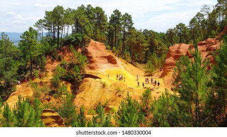 tourists walking in Sentiers des Ochres (Ochre Trail), beautiful yellow and orange hills scenery near Roussillon village in Luberon Valley, Vaucluse, Provence region, southern France, Europe