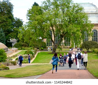 Tourists walking towards the Victorian Palm House in the Botanic Gardens in Edinburgh. Plant research centre and tourist attraction. Arboretum, Edinburgh Scotland. UK. July 2018