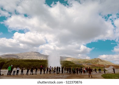 Tourists watching geyser erupting in Haukadalur, golden circle near Reykjavik in Iceland