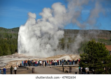 Tourists watching the Old Faithful erupting in Yellowstone National Park