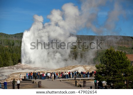 Tourists Watching Old Faithful Erupting Yellowstone Stock