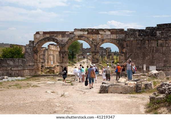 Tourists watching the ruins of Domitian Gate in ancient hellenistic city Hierapolis in Turkey