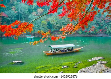 Tourists who go through the Ooi River in Arashiyama with a houseboat in Kyoto during the fall season.