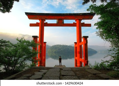 tourlist at red Torii gate of Hakone shrine located on lake Ashi, Japan. Gateways entrance to Shinto shrines and famous tourist landmar
