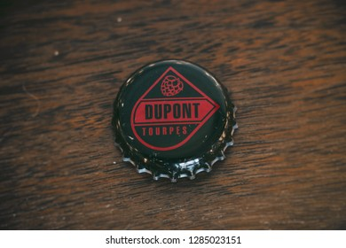 TOURPES, BELGIUM - JAN 14, 2019: Dupont Brewery beer bottle cap on wood table. Belgian beer known for their Saison Dupont, based in Tourpes, Belgium.