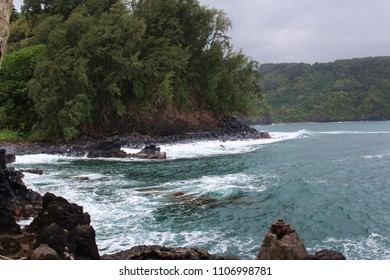 Tourquoise water from the Pacific Ocean flowing into a lava rock cove lined with lush vegetation at Wailua Lookout, Haiku, Maui, USA