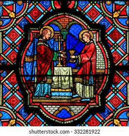 TOURS, FRANCE - AUGUST 14, 2014: Stained glass window depicting Jesus and a Saint with the Eucharist in the Cathedral of Tours, France.