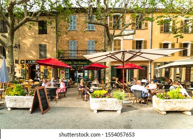 Tourtour, France - June 23 2019: People enjoy a coffee or a drink on an outdoor terrace in the traditional tourtour village in Provence